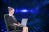 Businesswoman sitting on swivel chair with laptop — Stock Photo