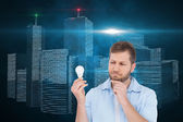 Composite image of sceptical model holding a bulb — Stock Photo