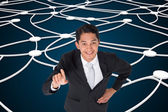 Composite image of smiling asian businessman pointing — 图库照片