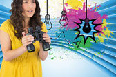 Composite image of serious casual young woman holding binoculars — Stock Photo