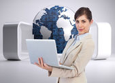 Confident young businesswoman with laptop — Stock Photo