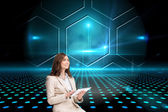 Businesswoman holding tablet and looking up — Stock Photo
