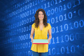 Composite image of smiling curly haired brunette holding notebooks — Stock Photo