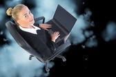 Блондинка бизнесвумен, сидя на вращающееся кресло с ноутбуком — Стоковое фото