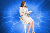 Composite image of happy businesswoman using tablet — Stock Photo