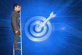 Stern businessman standing on ladder peering — Stock Photo
