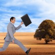 Composite image of businessman running with a suitcase — Stock Photo #38532273