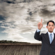 Composite image of serious asian businessman pointing — Stock Photo #38533659