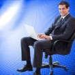 Businessman sitting on an armchair working with a laptop — Stock Photo