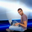 Man wearing glasses sitting on floor using laptop — Stock Photo #38537349