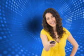 Composite image of smiling curly haired pretty woman changing channel with remote — Stock Photo