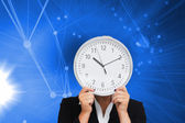 Businesswoman in suit holding a clock — Stock Photo
