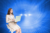 Composite image of smiling businesswoman sitting and using laptop — Stock Photo