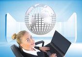 Zusammengesetztes bild der geschäftsfrau sitzt auf drehstuhl mit laptop — Stockfoto