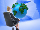 Composite image of businesswoman sitting on swivel chair in black — Stock Photo