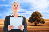 Composite image of businesswoman holding tablet — Stock Photo