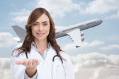 Composite image of portrait of female nurse holding out open palm — Stock Photo