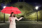 Composite image of happy businesswoman holding umbrella — Stock Photo