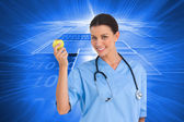 Surgeon holding an apple and smiling at camera — Stock Photo