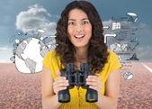 Young woman holding binoculars — Stock Photo