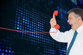 Businessman screaming directly into the red telephone handset — Stock Photo