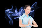Composite image of peaceful young businesswoman praying — Stock Photo