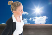 Composite image of businesswoman standing with hands on hips — ストック写真