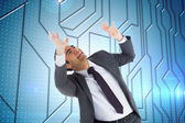 Composite image of scared businessman with arms raised — Stock Photo