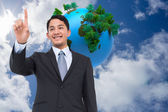 Composite image of smiling asian businessman pointing — Stock Photo