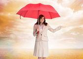 Happy businesswoman holding umbrella — Stock Photo