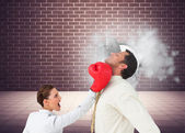 Businesswoman hitting a businessman with boxing gloves — Stock Photo