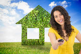 Smiling curly haired pretty woman changing channel with remote — Stock Photo