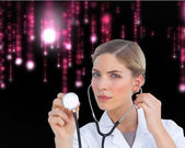 Serious nurse listening with stethoscope — Stock Photo