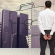 Composite image of rear view of young businessmwearing handcuffs — Stock Photo #38540785