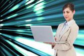 Composite image of confident businesswoman holding laptop — Stock Photo