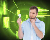 Sceptical model holding a bulb — Stock Photo