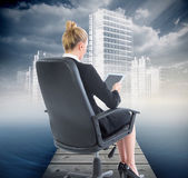 Composite image of businesswoman sitting on swivel chair with ta — Foto de Stock