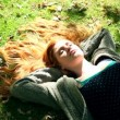 Stock Video: Young redhead relaxing on lawn