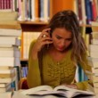Stock Video: Focused student studying in the library surrounded by books