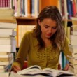 Pretty student studying in the library surrounded by books — Stock Video