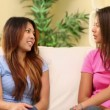 Stock Video: Two pretty sisters sitting on couch chatting