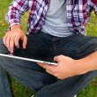 Student sitting on the grass using his tablet — Stock Video