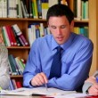Stock Video: Serious lecturer helping his students in library