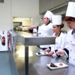 Stock Video: Head chef inspecting his students desserts