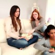 Stock Video: Pretty young friends eating popcorn while watching television