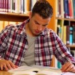 Stock Video: Concentrating student studying in library