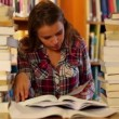 Attentive student studying in the library surrounded by books — Stock Video