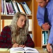 Lecturer helping blonde student in the library — Stock Video #38903593