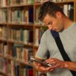 Stock Video: Concentrating student using his tablet standing in library