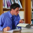 Stock Video: Serious lecturer preparing class in library